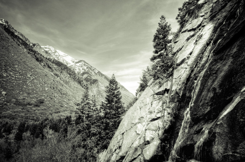 A waterfall gently falls down the rock face in Little Cottonwood Canyon during the snow melt.
