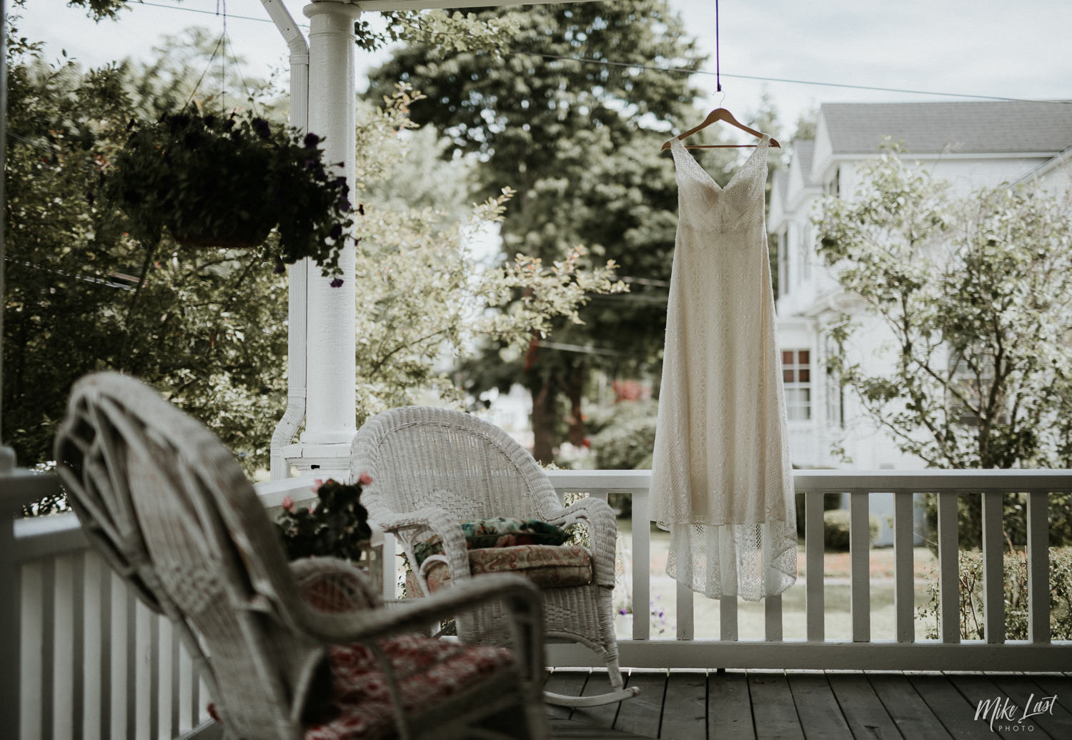 Wedding dress hanging on covered porch of century home in Liverpool, Nova Scotia.