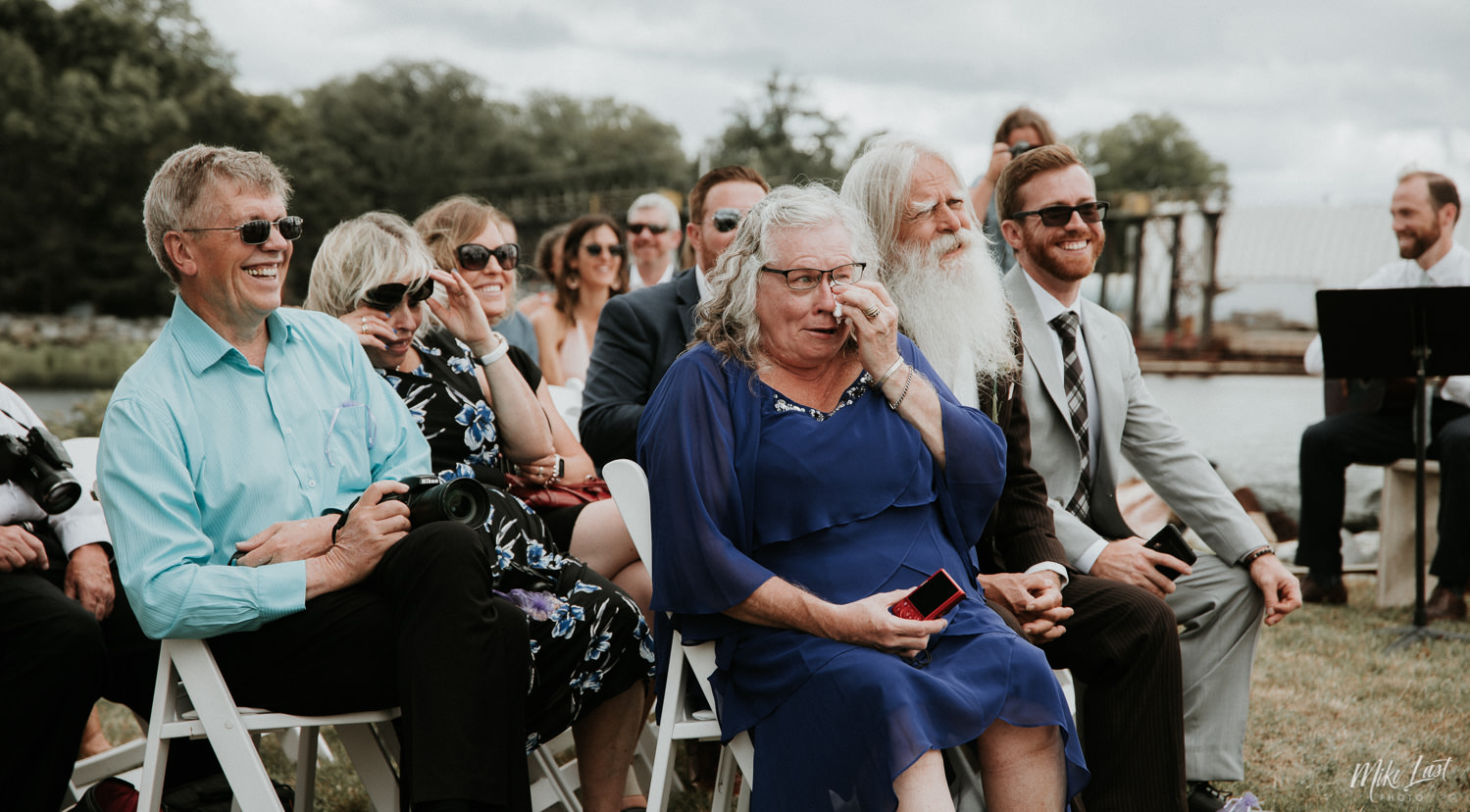 Mother of the groom drying tears of laughter at wedding.