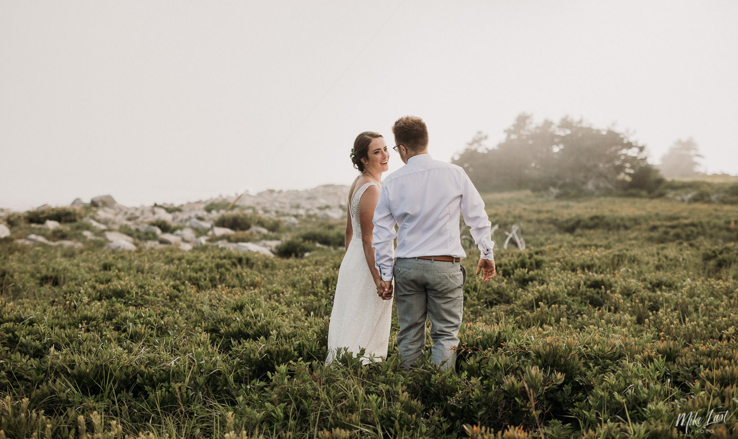 Bride and groom walking through the fog at Western Head Lighthouse.