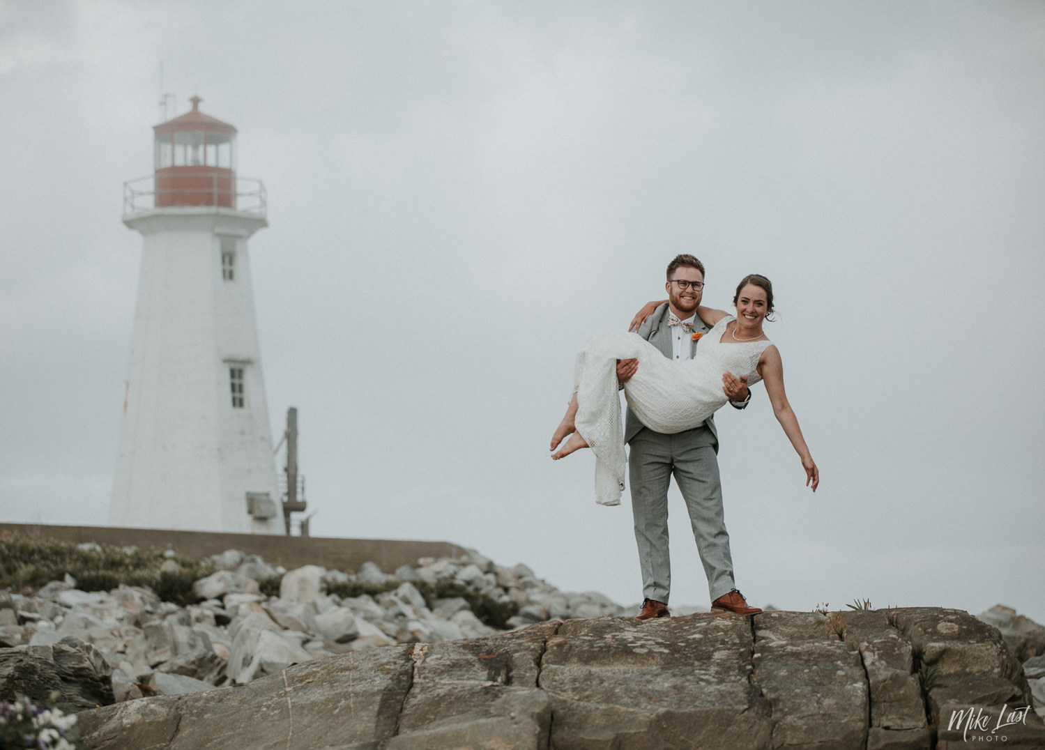 Groom sweeping bride off her feet in front of Western Head lighthouse in Nova Scotia