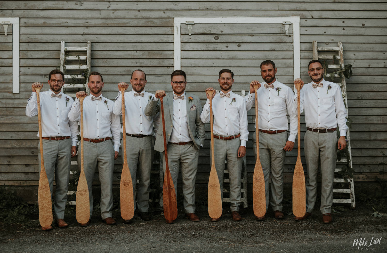 Groom and groomsmen with matching paddles form bachelor party canoe trip.