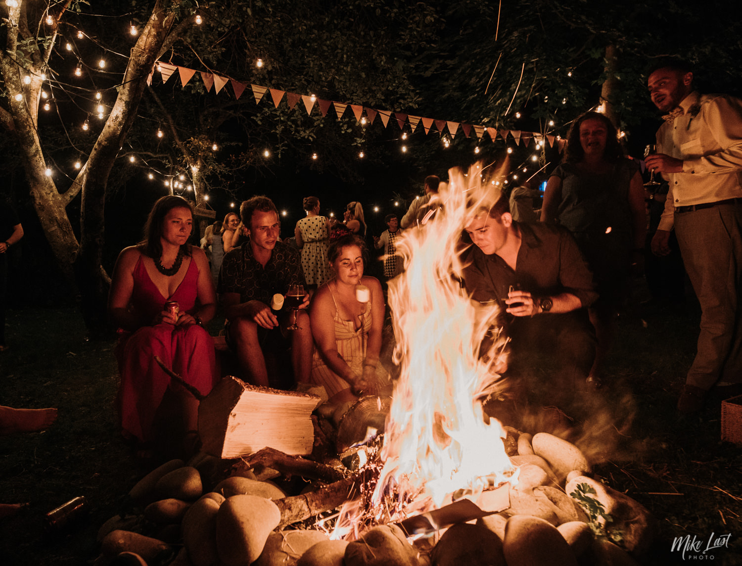 Backyard wedding campfire with marshmallows under string lights.