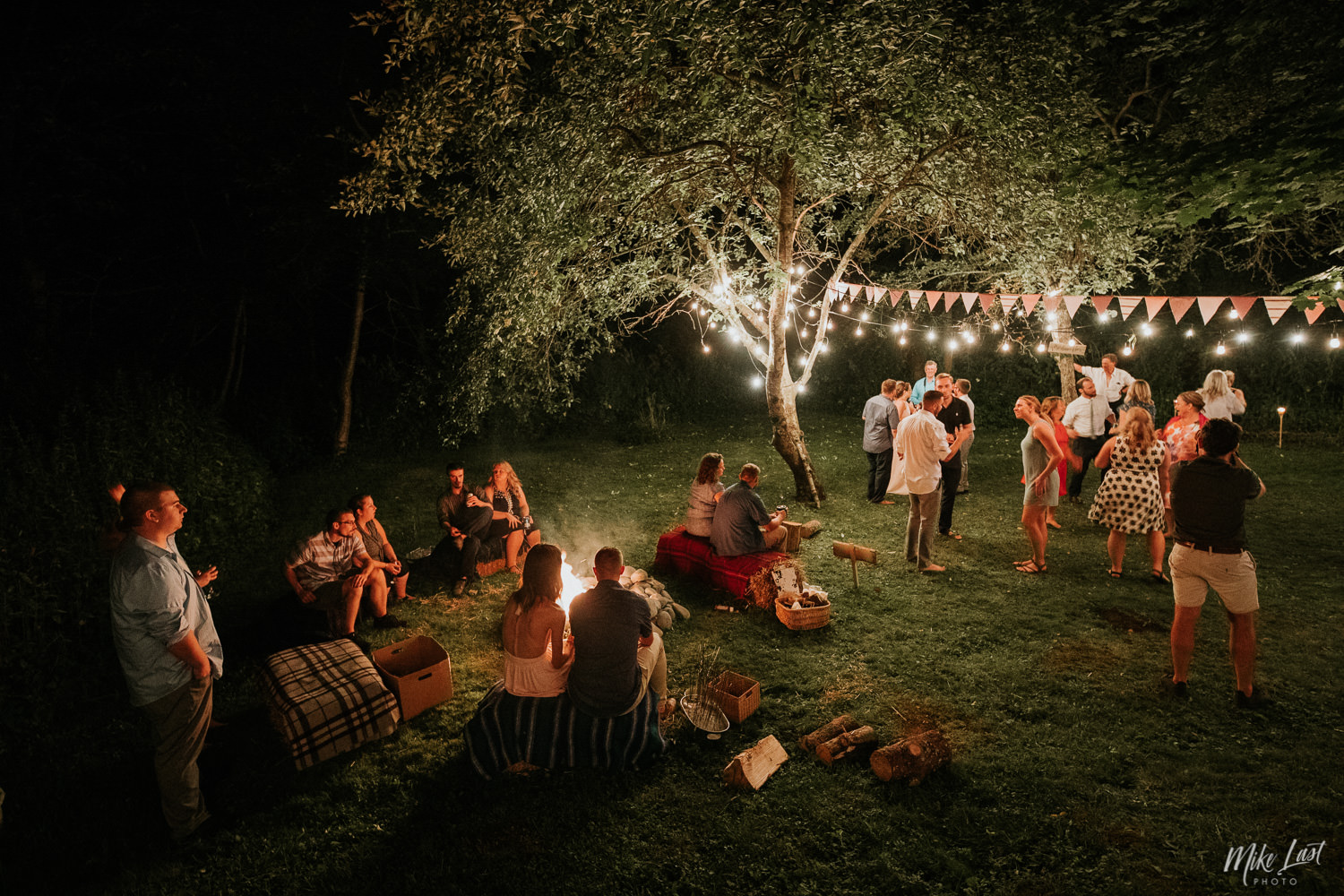 Nova Scotia backyard wedding under string lights with a camp fire.